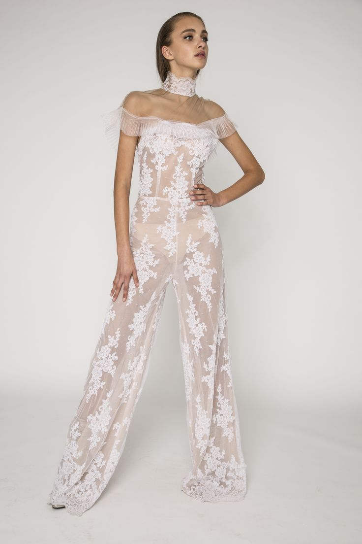 Vintage lace embellished sheer jumpsuit with off the shoulder pleated japanese organza detailing and lace high neck. The Romi dress is a vintage lace embellished sheer jumpsuit. The off the shoulder pleats created with japanese organze detailing and the lace high neck detail all contribute to the overal vintage look.The jumpsuit has been designed for a slim fit and has wide pant legs. #bridal #floral #lace #widepantleg #illusion #vintage #NARCES