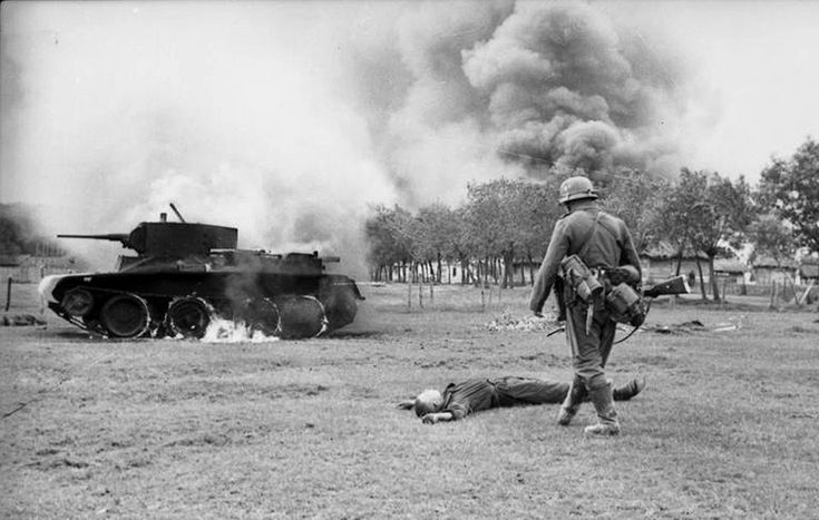A German infantryman walks toward the body of a killed Soviet soldier and a burning BT-7 light tank in the southern Soviet Union in in 1941, during the early days of Operation Barbarossa. (Deutsches Bundesarchiv/German Federal Archive)