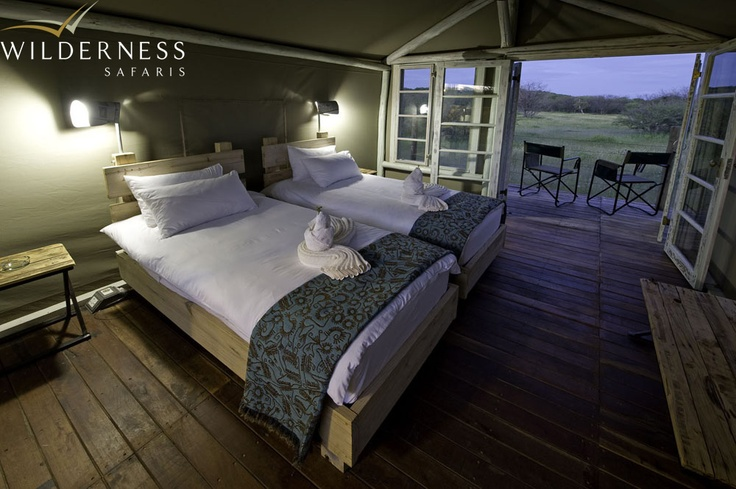 Andersson's Camp - Tents are a clever mix of calcrete stone cladding, canvas and wood, with double-door entrances and a small veranda that is an extension of the elevated wooden decks on which the tents are constructed. #Safari #Africa #Namibia #WildernessSafaris