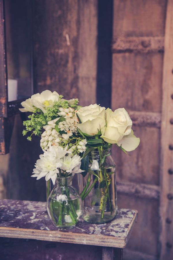 Rustic jars filled with ranunculus, roses, alstromeria, pieris, blushing bride, carnations, chrysanthemums, anenomes and more sat on the wedding venue tables and a rustic ladder a the entrance to the reception.