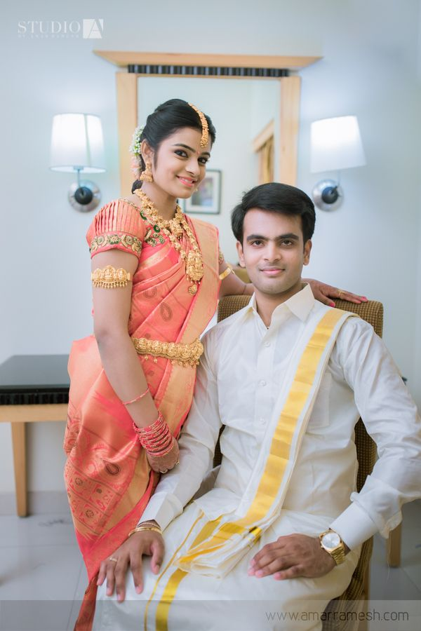 South Indian Bride in Salmon Pink Shaded Saree with Heavy Gold Jewelry with Groom in White and Gold