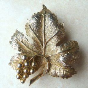 Pretty vine leaf brooch with grapes brooch by W A P Watson manufactured under the trade name Exquisite.  The brooch design features a  large vine leaf with fruiting grapes, in textured and polished gold tone metal.   Signed Exquisite to the back of the brooch. Circa 1960's.
