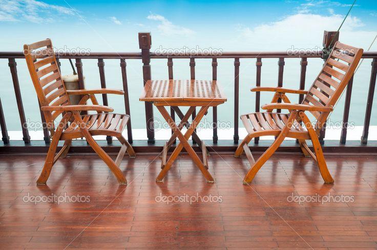 Lege houten dek stoelen en tafel op het schip permanent in de buurt van Houten spoor. blauwe bewolkte hemel op achtergrond. comfortabele boot tour. Cruise en zee reizen op zomervakantie