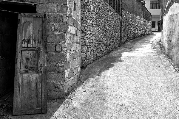 The primary reason to visit Xingyi in southern China's Guizhou province is moutainous scenery, particularly Wanfenglin (The Forest of Ten Thousand Peaks). After a guided tour to a series of scenic vistas, we left our tour to explore a local village on foot and discovered this alley. #blackandwhite #alley #stone