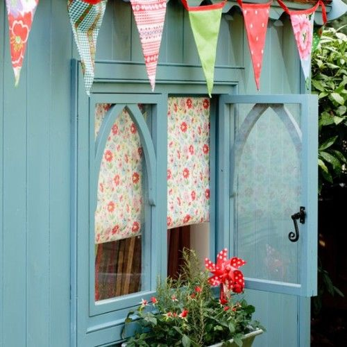 Pretty painted shed with bunting and window box