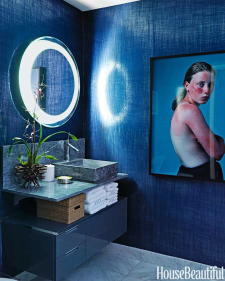 The guest bath strikes a dramatic note with walls covered in shimmering Paradisio Cristal fabric by Elitis.