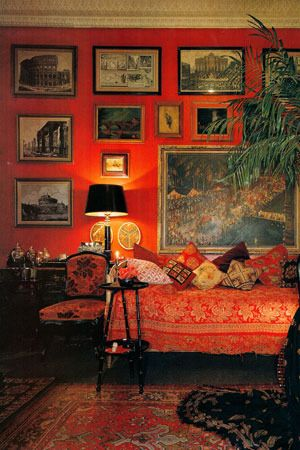 Red oriental rug, red wall, red and gold bed cover, art.