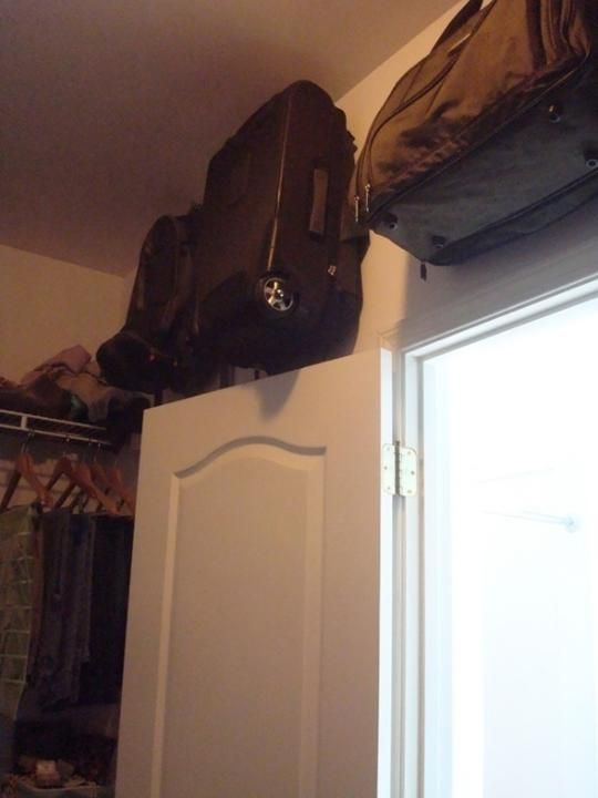 Hang suitcases in awkward spaces on hooks, many great ideas on this link for small closet organization.