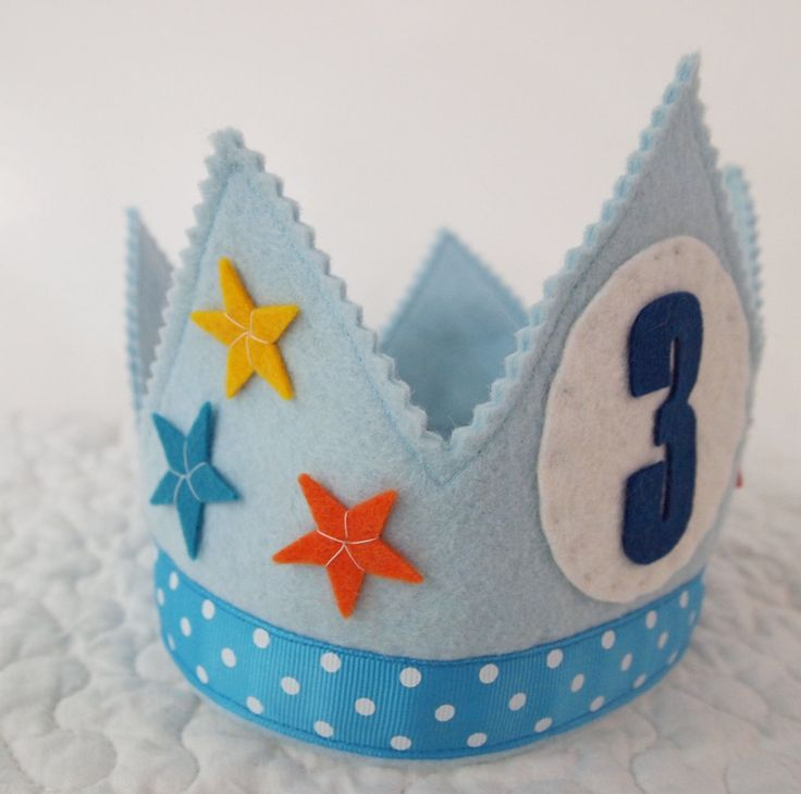 Heres a colorful birthday crown made especially for your birthday boy! Six stars are hand stitched to this powder blue crown. Our festive teal polka-dot ribbon makes it perfect for birthdays!  Our birthday crowns are made from heirloom quality wool felt, making them durable and sure to last through the years. We use woven ribbon ties to secure the crown to your childs head.  Fits age 1 and up! Care Instructions: Spot Clean Only…