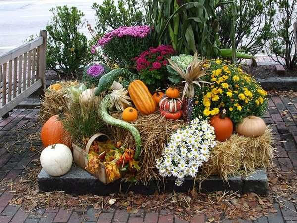Festive Outdoor Fall Arrangement with Mums, Gourds and Pumpkins on Bales of Hay.