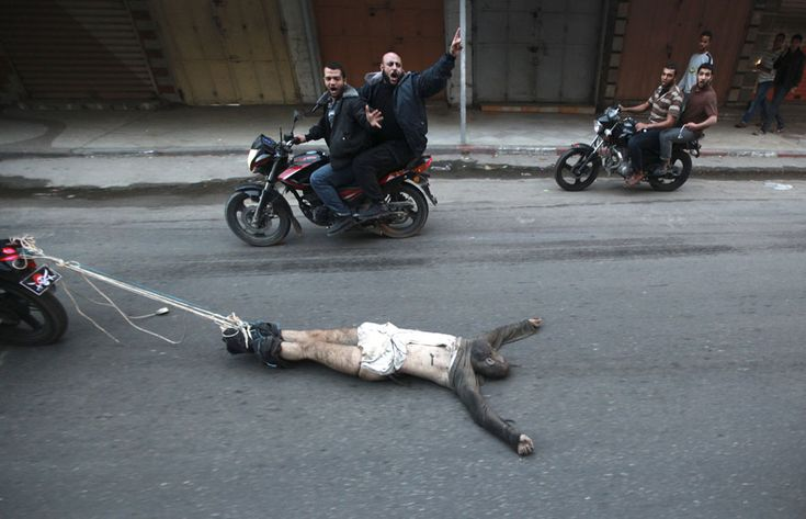 """Caption: Palestinian gunmen ride motorcycles as they drag the body of a man, who was suspected of working for Israel, in Gaza City November 20, 2012. Palestinian gunmen shot dead six alleged collaborators in the Gaza Strip who """"were caught red-handed"""", according to a security source quoted by the Hamas Aqsa radio. MOHAMMED SALEM, Gaza"""