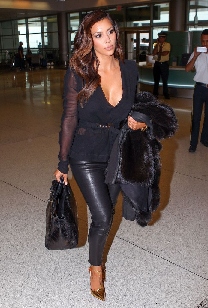 Sexy black top with leather pants and golden heels.