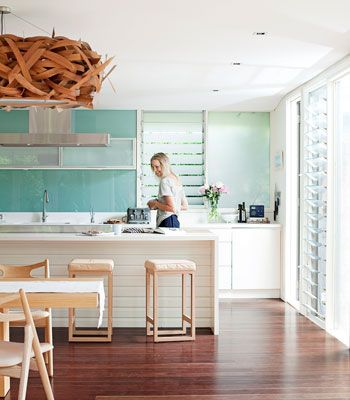 Here, the louvered windows, wooden stools and tongue- and-groove panelling at the facing side of the island bench all signal a relaxed lifestyle. But it's the decision to separate the room into two halves that distinguishes this kitchen. The lower half is kept white and natural, while the top half, reflective glass that's been tinted aqua, suggests an expanse of sky.