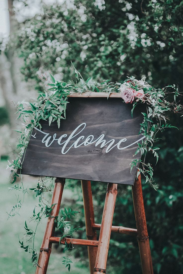 Chalkboard wedding welcome sign with floral garland on bamboo stand | Stories by Bianca via Paper and Lace