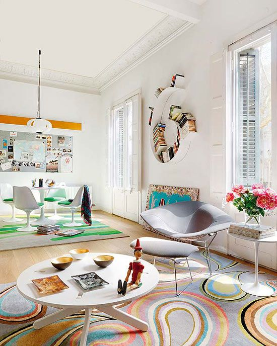 High ceilings and abundant natural light are the best features of this colorful 19th-century apartment in Barcelona, Spain, where furniture design, brilliant layout and ingenious solutions create pleasant surprises. Architects Angle Borras and Elodie Grammont from Miel Arquitectos Studio came up with an unusual triangular floor plan using the diagonal hallway to connect all the different rooms.