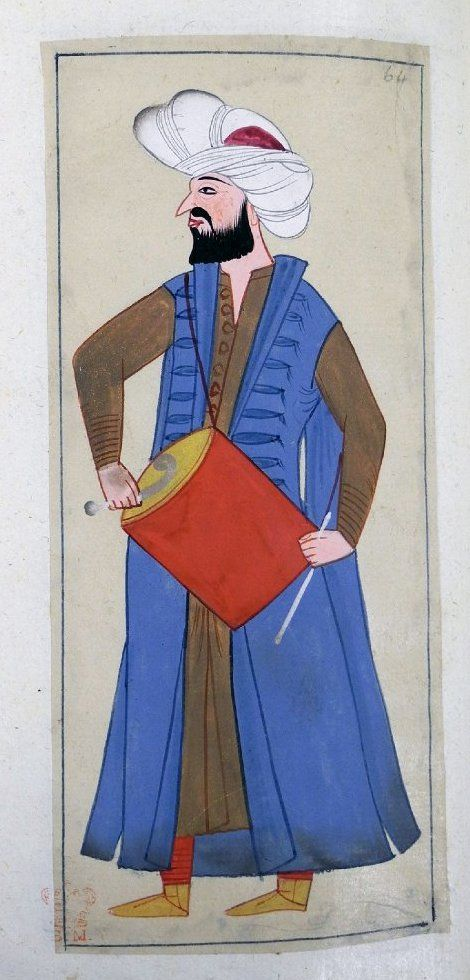 Davulcu. A mehtar drummer. Wearing wide turban but no plume, blue kaftan, brown robe, red trousers and yellow ankle boots. The drum is slung round his neck by a red cord. Two types of drumsticks, a straight white one and a curved stick.