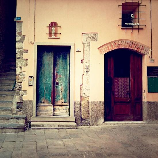 turquoise-y door; creamy exterior wall; grey slate and a deep brown door.