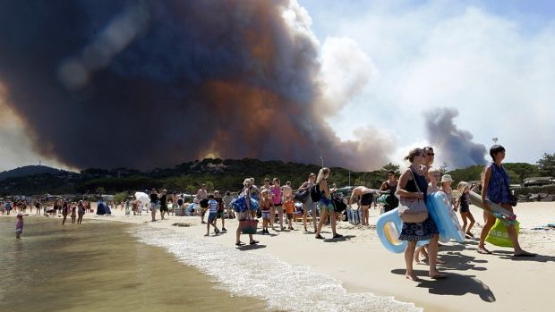 French authorities ordered the evacuation of up to 12,000 people around a picturesque hilltop town in the southern Cote d'Azur region of the French Riviera as fires burned around the Mediterranean coast for a third day Wednesday.