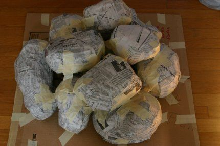 A before picture of a pile of faux rocks made from cardboard and plastic containers covered with sheets of newspaper taped together and then covered with smaller pieces of newspaper soaked in white glue.