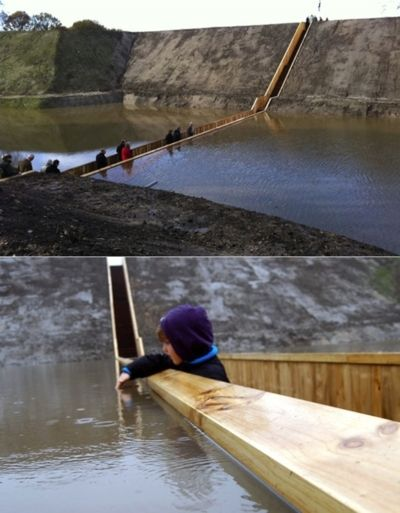 The Moses Bridge, as its name suggests, is pedestrian bridge that creates the illusion of walking through water — the West-Brabant waterline near Fort de Roovere in the Netherlands.