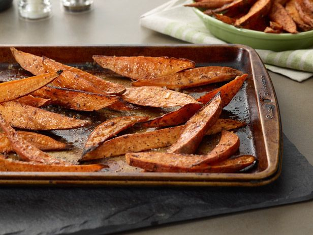 Baked Sweet Potato Wedges from FoodNetwork.com - Toss thick-cut sweet potato wedges in cinnamon-spiced butter and bake until crispy for an easy side dish or snack.