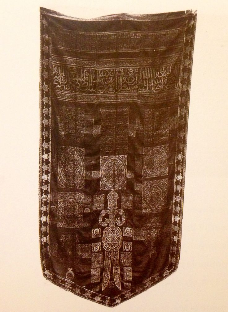 Ottoman banners woven during the 15th century are often decorated with a two-bladed sword wielded by the prophets son-in-law Ali and shield shaped. This particular banner, made in 1683 in North Africa, was made of metallic thread and maroon silk. Its inscription is written in the distinctive maghribi script with uniform thick letters and low sweeping curves.