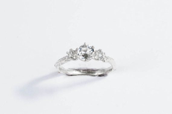 This three stone twig ring features a beautiful AAA grade 5mm faceted white topaz. The two side stones are AAA 3mm white topaz. The prongs are cast in