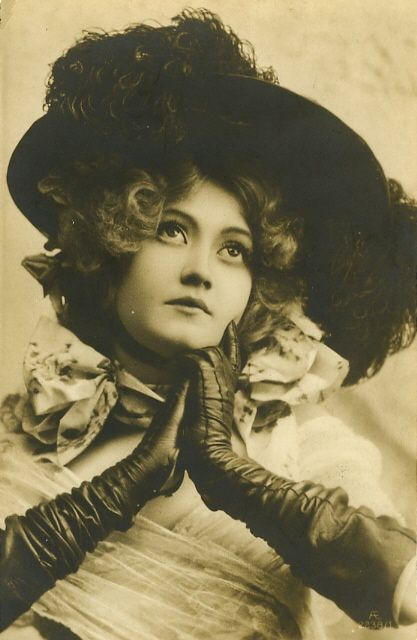 Vintage portrait of woman in hat and leather gloves.