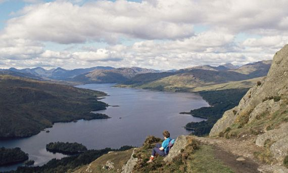 A walker relaxes and takes in the view at the summit of Ben A'an, overlooking Loch Katrine