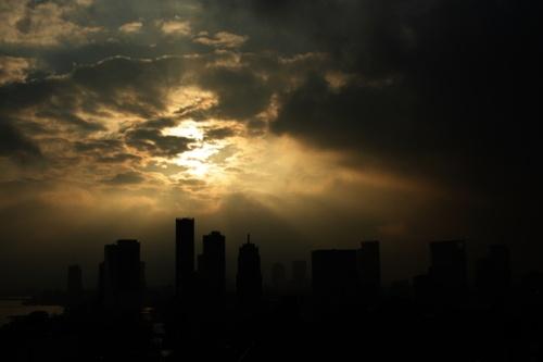 de donkere stad tegen het licht van de zon die door de wolken gekropen komt. dus een licht donker contrast. erg mooi.
