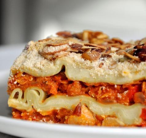 Pompoenlasagne: tomatengroentensaus met veel pompoen en linzen, bechamelsaus van sojamelk, -boter en groentenbouillon,, lasagnevellen, paneermeel en geroosterde nootjes