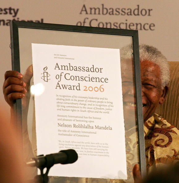 South Africa's former president Nelson Mandela holds his Amnesty International 'Ambassador of Conscience' Award for 2006 in Johannesburg 01 November...