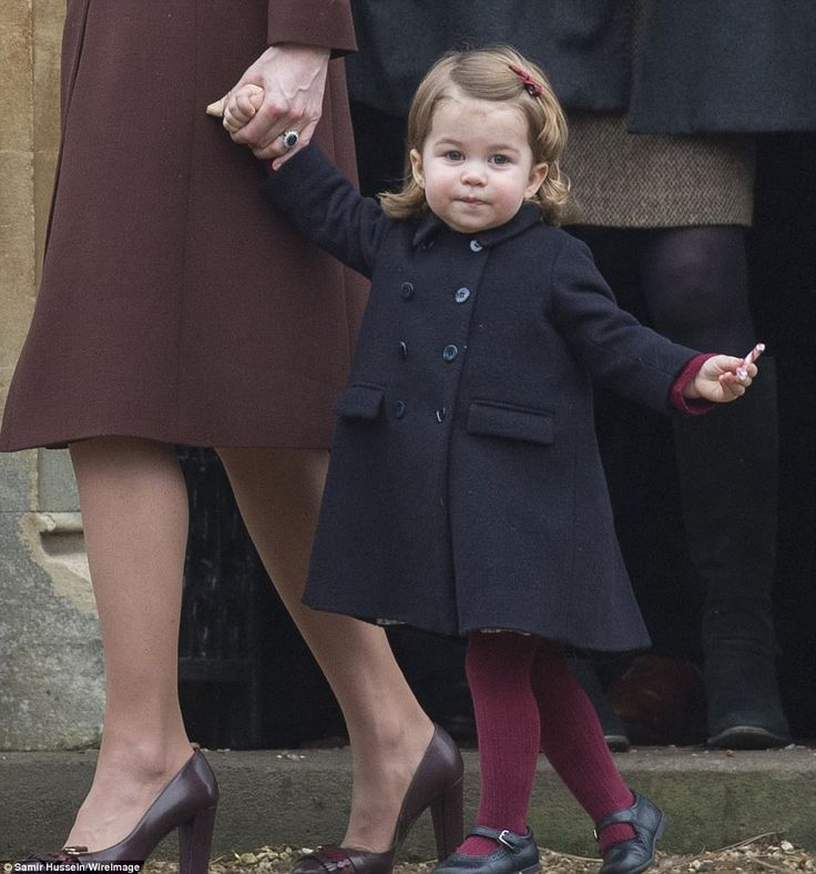 Clutching a traditional red and white striped candy cane with one her and her mother with the other, Charlotte attends church in the village of Buckleberry, the Middleton family's West Berkshire home, on Christmas Day last year
