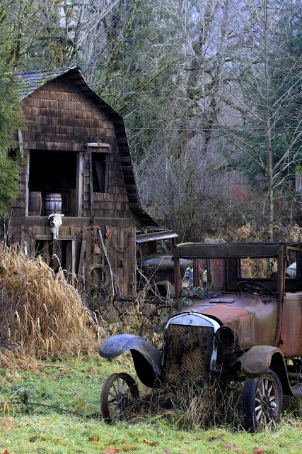 A retired automobile rests quietly next to an old barn.