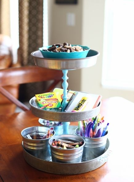 A three-tiered organization station made from silver pie tins and candlesticks painted blue