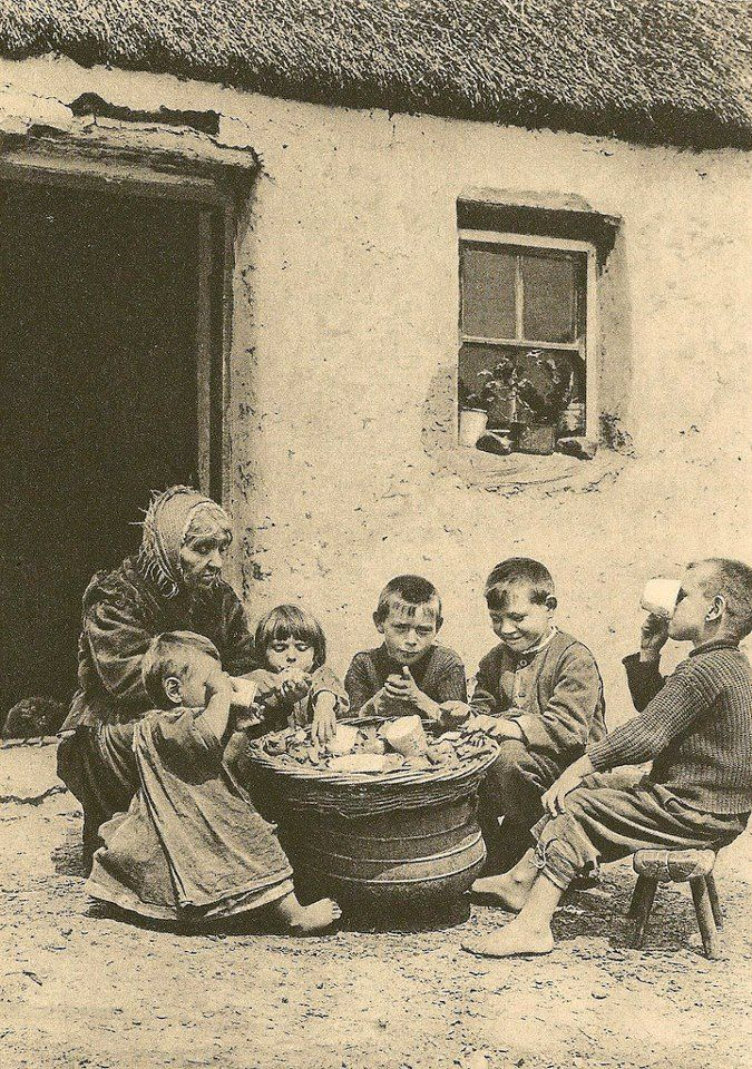 AT THE POT, CIRCA 1915-1922   This photograph by A.W. Cutler shows five barefoot children eating potatoes from a basket, and drinking milk outside a thatched cottage in Ireland, accompanied by an older woman. It was published in National Geographic but I am not sure which year -- Wistorical