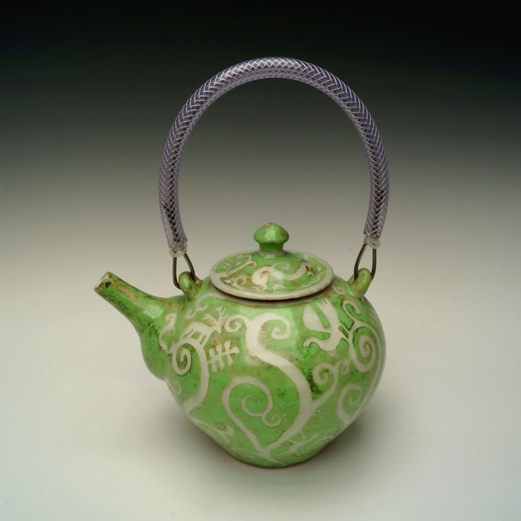 A green teapot with resist decoration. Stoneware, reduction fired, stainless steel and poly-pipe handle.