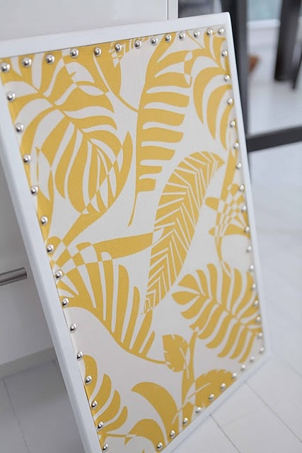 DIY cork board w/ custom fabric overlay nailhead detail.