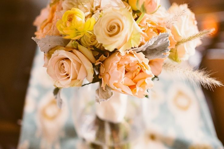 Bridal bouquet of Sahara and Campanella garden roses, ranunculus, fountain grass, and dusty miller.