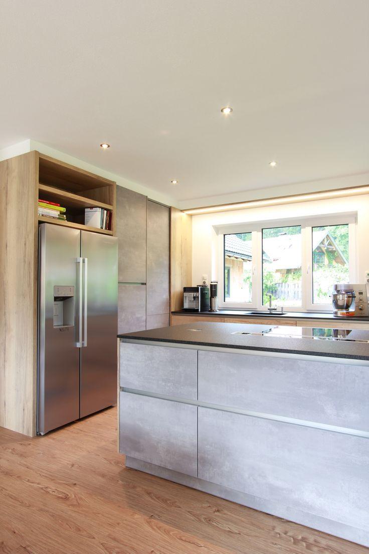 Küche in Beton-Optik mit freistehendem amerikanischem Kühlschrank. Schwarze Natursteinarbeitsplatte und Dunstabzug nach unten für viel Kopffreiheit über der Kochinsel