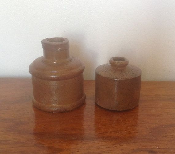 A pair of English Stoneware brown ink pots , from the early 1900s. Both in good condition with no cracks...but all the usual discolouration and marks which give that wonderful rustic feel.  The larger pot is just under 3 tall by 2.2 diameter, one tiny chip on top The smaller one is 2 tall by 1.7 diameter.  I have shown all angles so you can see all the age related marks.  Please note: We are happy to post our vintage items anywhere in the world. As they would be sent tracked and signed for…