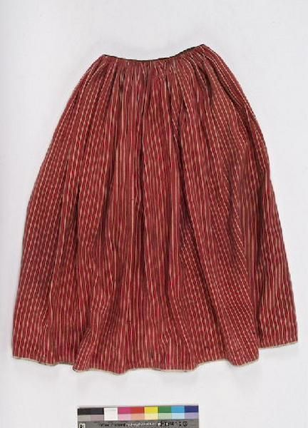 Jupe de paysanne en coton épais rayé rouge, froncée à la taille. Elle correspond à ce qui était porté dans les campagnes pendant toute la seconde moitié du 19e siècle