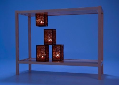 "a table inspired by floating luminarias | lit with candles | eastern maple, canary wood, afromosia | 38""L x 14""D x 29""H"