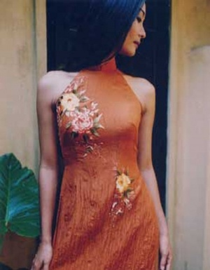 Modern ao dai in orange with embroidered flowers and glass bead artwork.