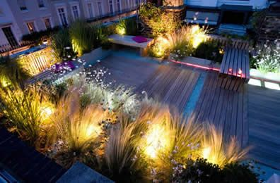 decked roof terrace garden at night by the amazing charlotte rowe, garden designer.