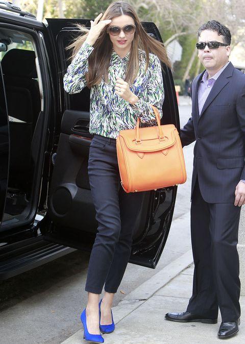 Siempre elegante, Miranda sabe como traer la primavera a un look working. Esta vez combina sus pantalones negros con una blusa estampada, salones en azul Klein y bolso de mano naranja vitamina.