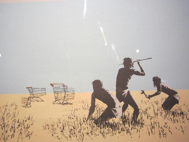 de tekeningTrolleyswaarop een groepje primitieve manfiguren staan te kijken naar winkelwagentjes. Je vraagt je af wat de mannen gaan doen. In de aanval of slaan ze op de vlucht? Of zijn deze mannen juist op jacht?- Banksy