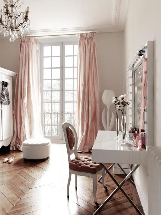 Glam pink closet with floor to ceiling French doors covered in blush pink silk pinch-pleat curtains, pale gray walls paint color, glossy white lacquer vanity with polished nickel legs, French oval back pink velvet tufted chair, wood floors in herringbone chevron pattern, white tufted round ottoman and white armoire. decorpad.com via Elle Decor