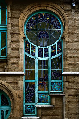 Early 20th century Transitional stained glass window in Brussels, Belgium  Transitional: The period between the Art Nouveau and Art Deco movements, with designs that encompass both the sinuous, curvy lines of Nouveau and the more angular, geometric styles of Deco  (by Iskald)