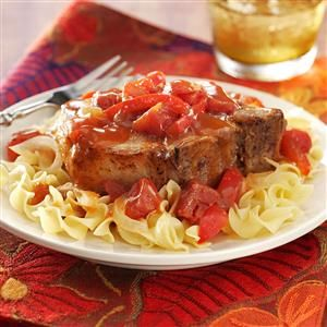 """Tangy Tomato Pork Chops Recipe -These tender chops are smothered in a delightfully rich sauce. """"I've used a chuck roast instead of pork loin chops, stewed tomatoes instead of diced and served it over rice. It's always good."""" —Lea Ann Schalk, Garfield, Arkansas"""